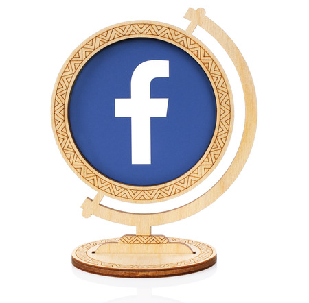 Kiev, Ukraine - November 01, 2017: Facebook circle icon printed on paper and placed into wooden globe on white background. Facebook is a well-known social networking service
