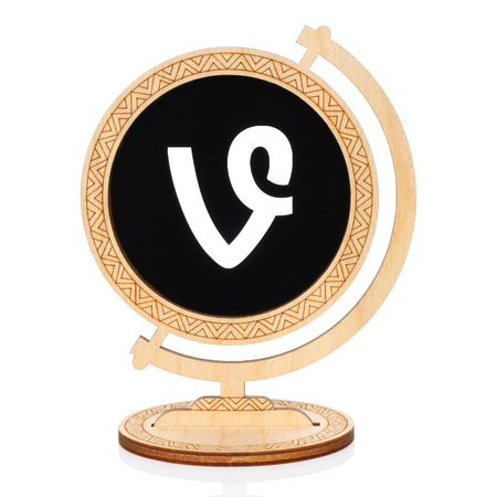 Kiev, Ukraine - November 01, 2017: Vine circle icon printed on paper and placed into wooden globe on white background. Vine is video hosting service where users could share video clips