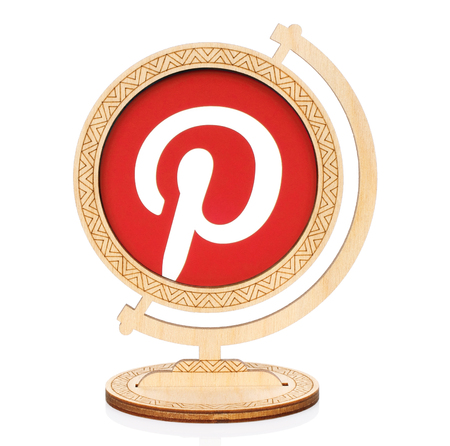Kiev, Ukraine - November 01, 2017: Pinterest circle icon printed on paper and placed into wooden globe on white background. Pinterest is a web and mobile application for discover information