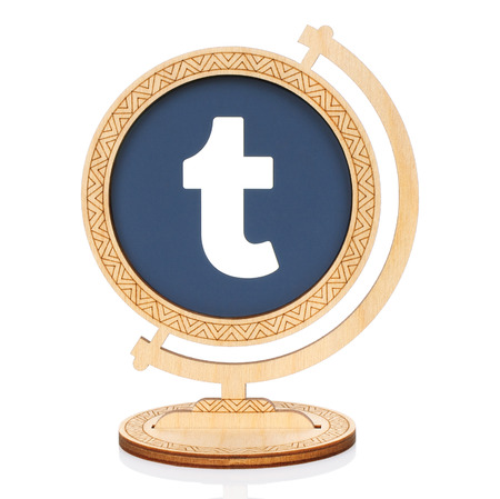 Kiev, Ukraine - November 01, 2017: Tumblr circle icon printed on paper and placed into wooden globe on white background. Tumblr is a microblogging and social networking website