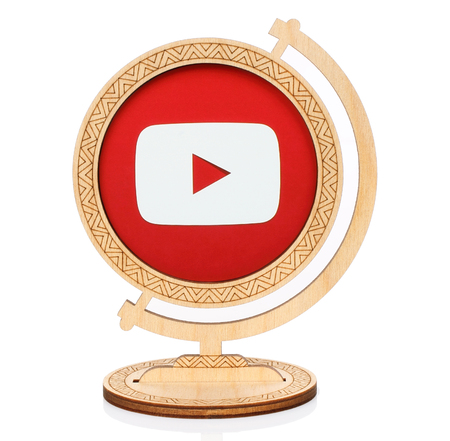 Kiev, Ukraine - November 01, 2017: Youtube circle icon printed on paper and placed into wooden globe on white background. YouTube is an American video-sharing website