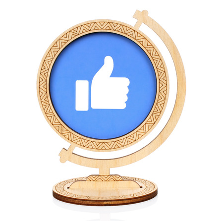 Kiev, Ukraine - November 01, 2017: Facebook Like circle icon printed on paper and placed into wooden globe on white background. Facebook is a well-known social networking service Editorial