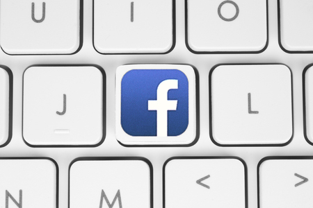 Kiev, Ukraine - May 06, 2016: Facebook logo printed on paper and placed on white computer keyboard. Facebook is a well-known social networking service