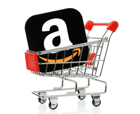 Kiev, Ukraine - November 01, 2017: Amazon icon printed on paper and placed into shopping cart. Amazon is an American electronic commerce and cloud computing company 報道画像