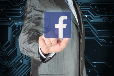 Kiev, Ukraine - February 12, 2018: Businessman pushes Facebook icon on circuit board background. Facebook is a well-known social networking service Editorial