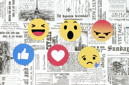 Kiev, Ukraine - February 08, 2018: Facebook like button 6 Empathetic Emoji Reactions printed on paper and placed on retro newspaper background. Facebook is a well-known social networking service