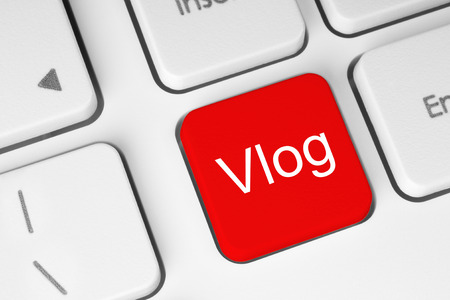 Red button with Vlog word on the keyboard close-up Imagens
