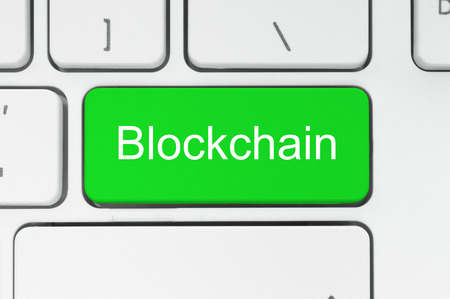 Blockchain concept. Green button with Blockchain word on the keyboard close-up