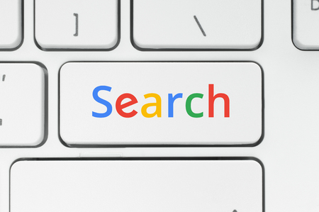 Search concept. Keyboard button with color Search word close-up
