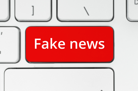 Fake News concept. Red button with Fake News words on the keyboard close-up Imagens