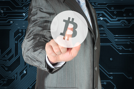 Businessman pushing virtual button with Bitcoin symbol on digital background