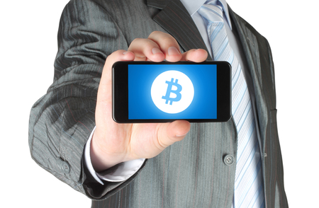 Businessman holds smart phone with Bitcoin symbol on circuit board background