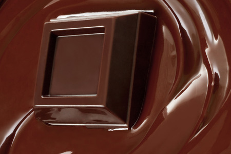 Melted chocolate dripping with chocolate bar close-up