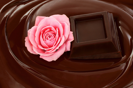 Melted chocolate dripping with chocolate bar and rose close-up