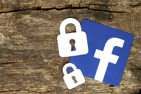 Kiev, Ukraine - May 04, 2017: Facebook icon with locks printed on paper and placed on old wooden background. Facebook security and privacy issues concept Editorial
