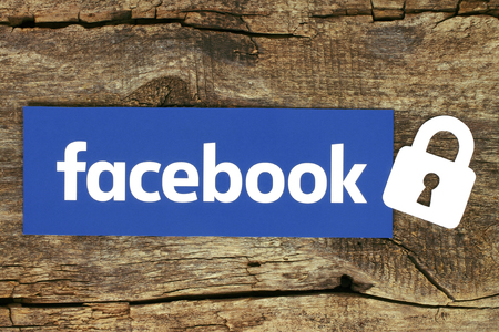 Kiev, Ukraine - May 04, 2017: Facebook logo with lock printed on paper and placed on old wooden background. Facebook security and privacy issues concept Archivio Fotografico - 113921628