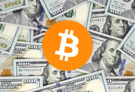 Bitcoin on hundred bills background