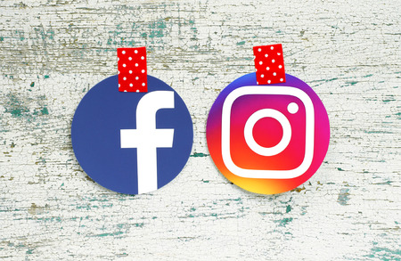Kiev, Ukraine - September 27, 2018: Facebook and Instagram round icons printed on paper and taped with red in white dots adhesive tape on old wood Editorial