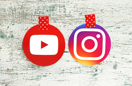 Kiev, Ukraine - September 27, 2018: YouTube and Instagram round icons printed on paper and taped with red in white dots adhesive tape on old wood