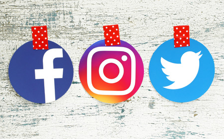 Kiev, Ukraine - September 27, 2018: Facebook, Instagram and Twitter round icons printed on paper and taped with red in white dots adhesive tape on old wood Editorial