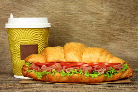 Big croissant with green salad, tomatoes and pork meat and paper coffee cup on old wooden background Imagens - 113967170