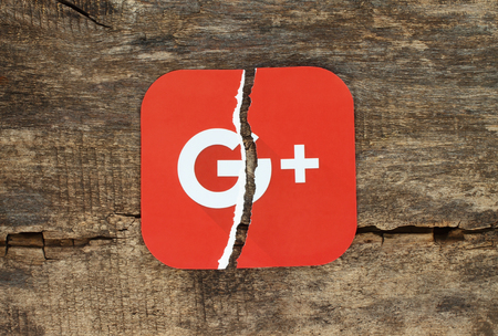 Kiev, Ukraine - November 07, 2018: Google plus icon printed on paper, torn and put on old wooden background. Google is shutting down Google+, admits low consumer adoption