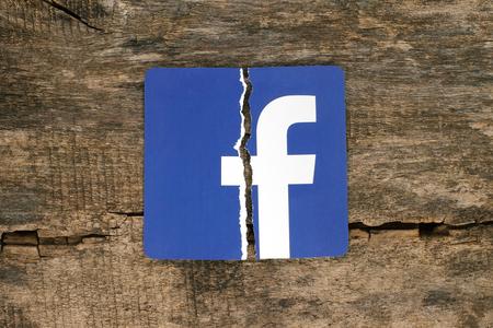 Kiev, Ukraine - 7 novembre 2018 : icône Facebook imprimée sur papier, déchirée et mise sur fond de bois ancien. Concept de problèmes de sécurité et de confidentialité de Facebook