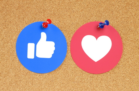 Kiev, Ukraine - November 28, 2018: Facebook Like and Love button of Empathetic Emoji Reactions printed on paper and pinned on cork bulletin board