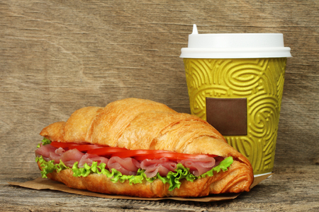 Big croissant with green salad, tomatoes and pork meat near paper coffee cup on old wooden background