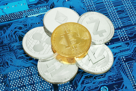 Cryptocurrency coins on circuit board background close-up