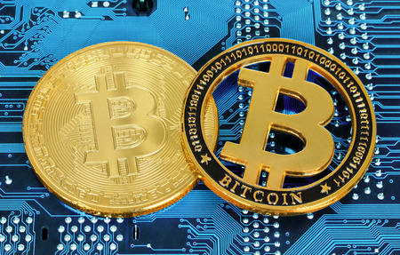 Bitcoin cryptocurrency coins on circuit board background close-up Reklamní fotografie