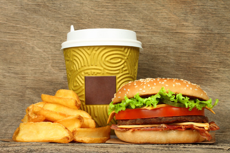 Big hamburger with french fries and paper coffee cup on old wooden background