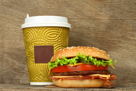 Big hamburger and paper coffee cup on old wooden background