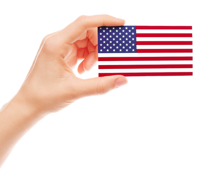 Hand holds American flag on white background close-up