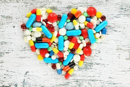 Color pills in the shape of heart on old wooden background close-up Reklamní fotografie