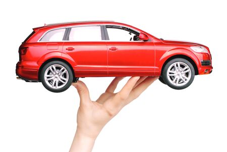 Kiev, Ukraine - May 15, 2019: Woman hand holding a big red car toy Audi on white background