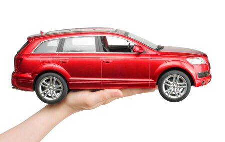 Kiev, Ukraine - May 15, 2019: Woman hand holding a big red car toy Audi on white background Stock fotó - 137017374