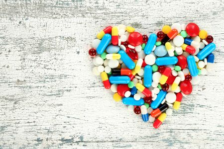 Color pills in the shape of heart on old wooden background close-up Stock fotó