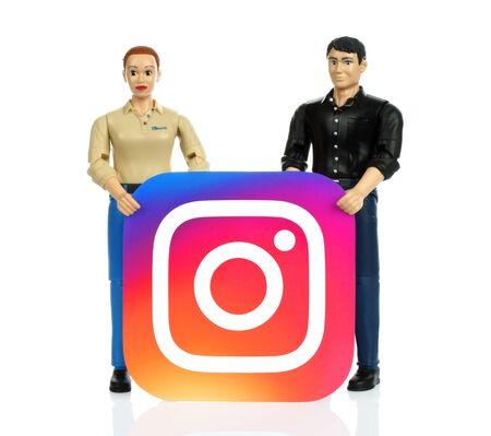 Kiev, Ukraine - October 29, 2019: Toys people holds Instagram paper logo. Instagram is an American photo and video-sharing social networking service owned by Facebook