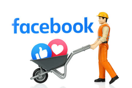 Kiev, Ukraine - November 27, 2019: Toy man holds wheelbarrow with Facebook Like and Love reactions. Facebook is a well-known social networking service