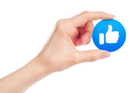 Kiev, Ukraine - May 15, 2019: Hand holds New Facebook Like icon printed on paper. Facebook is a well-known social networking service Editorial