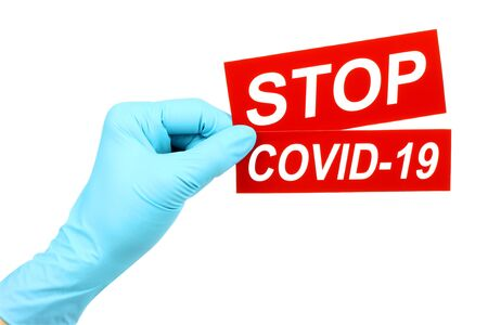 Woman hand in medical gloves holds red sign Stop Covid-19 on white background