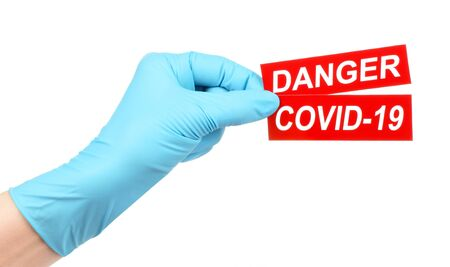 Woman hand in medical gloves holds red sign Danger Covid-19 on white background