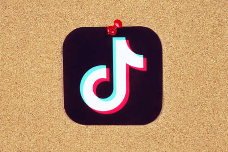 Kiev, Ukraine - August 25, 2020: TikTok icon printed on paper and pinned on wooden background. TikTok is a viral Chinese video-sharing social networking service owned by ByteDance