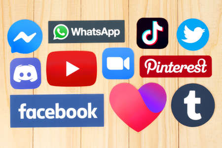 Kiev, Ukraine - August 25, 2020: Collection of popular social media logos printed on paper: Facebook, Discord, YouTube, Twitter, TikTok, WhatsApp, Pinterest, Zoom and Tumblr on wooden background