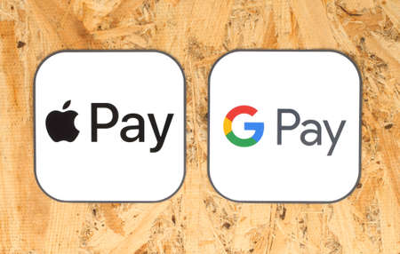 Kiev, Ukraine - August 25, 2020: Apple Pay and Google Pay icons printed on paper, on wooden background. Apple Pay is a mobile payment, digital wallet service. Google Pay is a digital wallet platform Editorial