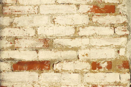 Texture background of old bricks wall with peeling paint close-up Standard-Bild