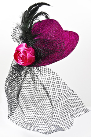 Bright pink  ladys hat with a black veil isolated on white - a carnival costume accessory photo