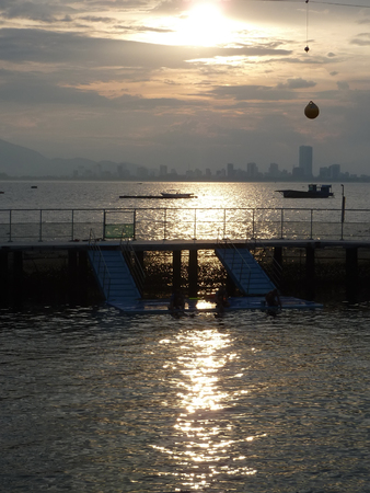 dolphinarium: Silhouette of Nha Trang city (Vietnam) in the golden rays of the setting sun reflected in the South China Sea. View from the dolphinarium