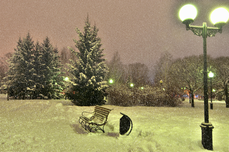 no snow: Romantic scene in a winter park. Heavy snowfall, but on the bench, illuminated by golden light of the lantern there is no snow. People just left.